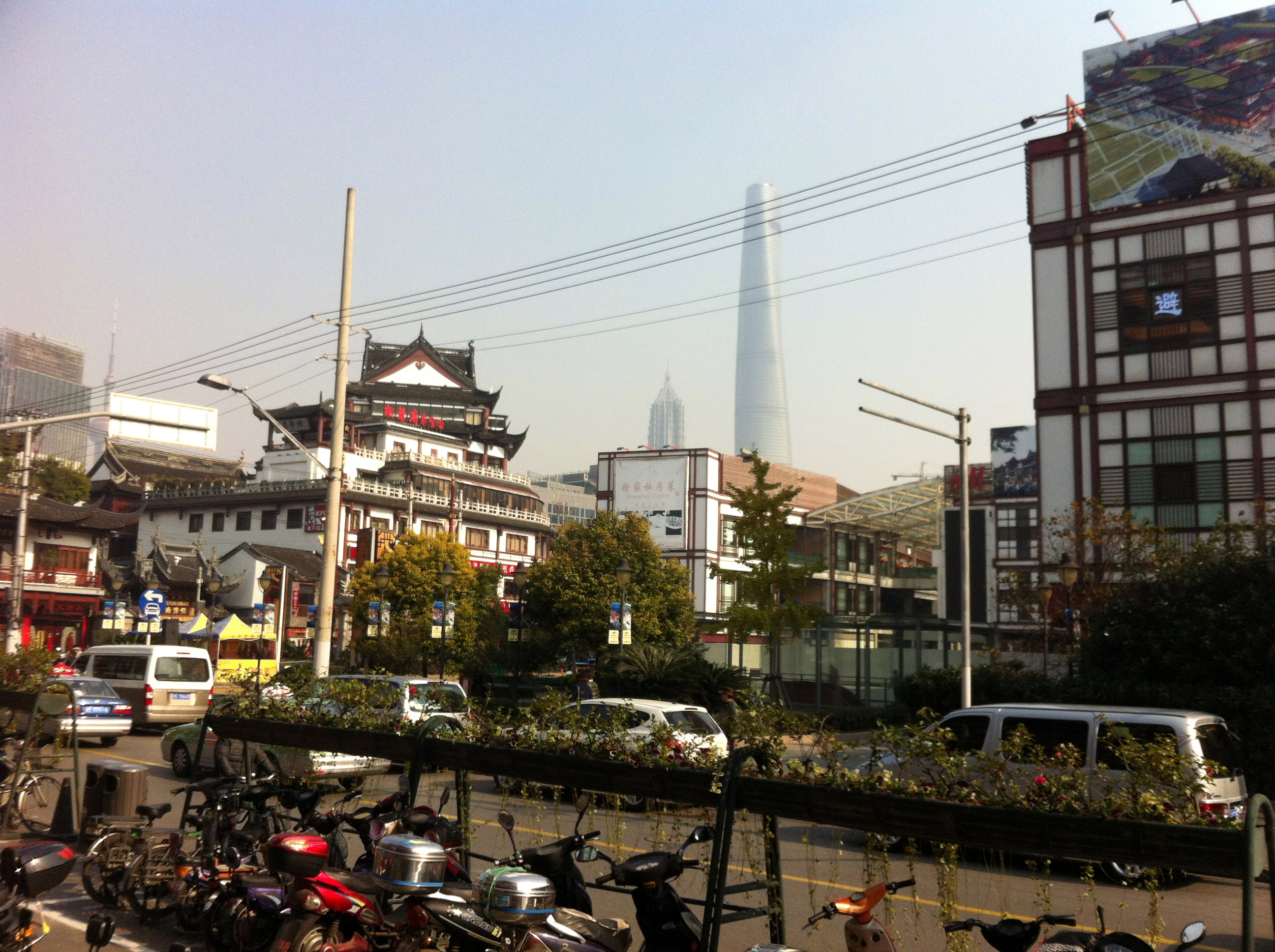 Modern scooters, older buildings, and modern towers all make up Shanghai's current incarnation.