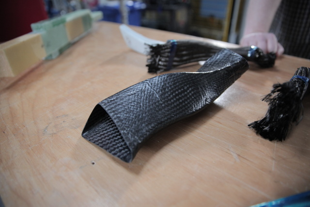 A finished model turbine component made from carbon fiber composite, with non-epoxied carbon fiber thread forms in the background.