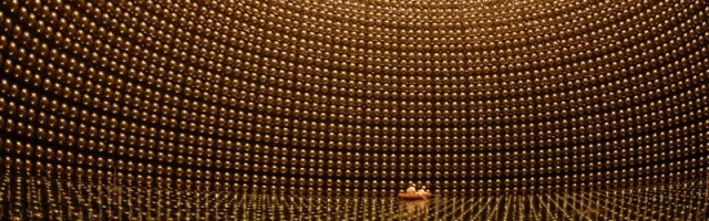 Two men in a rubber raft inspect the wall of photodetectors of the partly filled Super-Kamiokande neutrino detector.