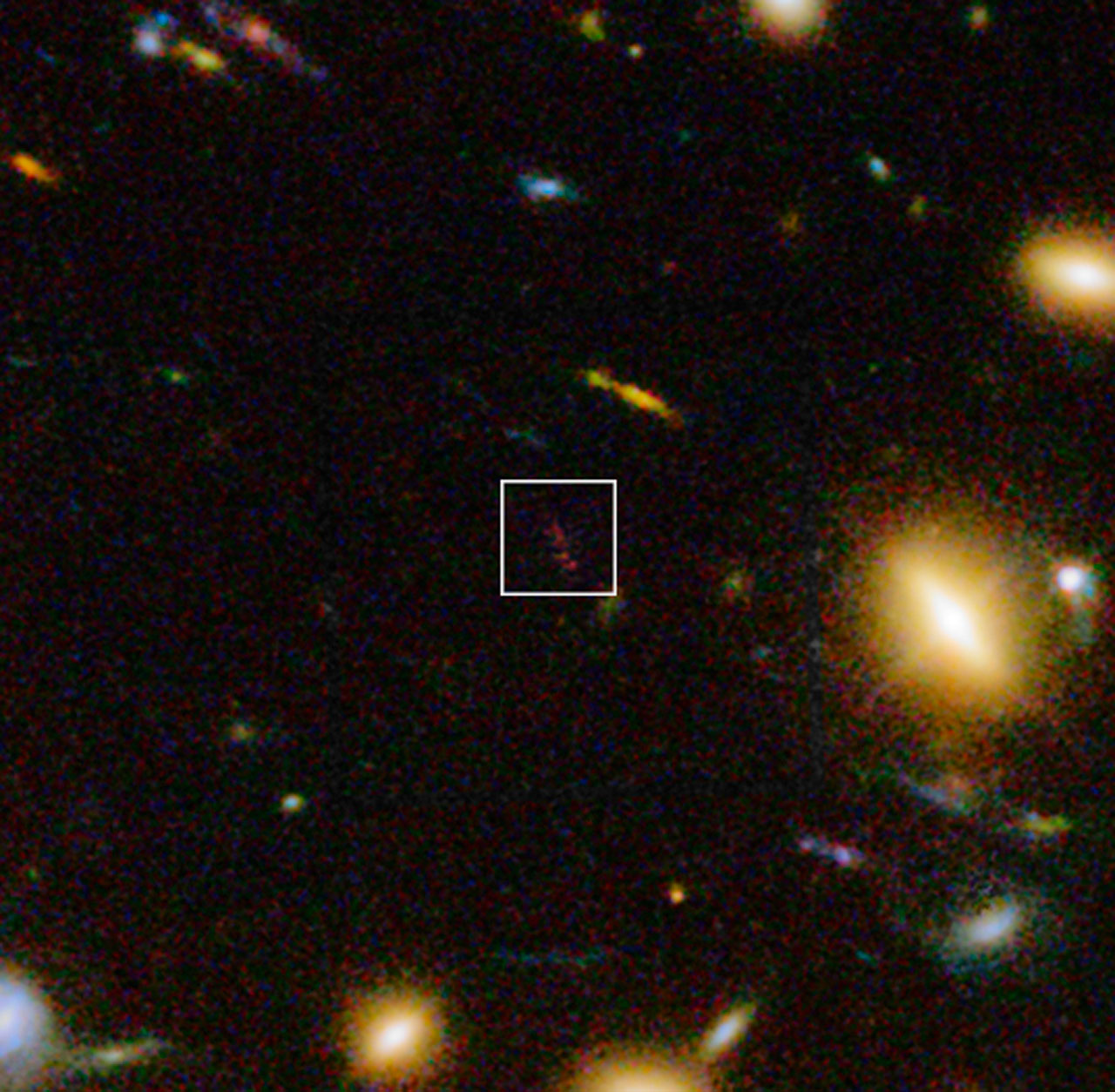"A ""close-up"" view of the region around A1689 zD1, made up of infrared images from the WFC3 device on the Hubble Space Telescope, as well as visible light views. The elongated reddish object in the box is zD1."