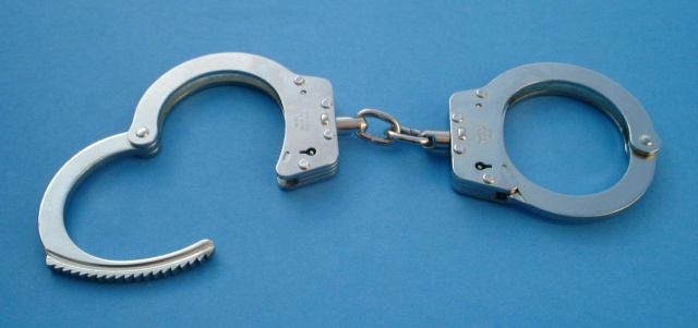 Handcuffs on a nondescript blue background.