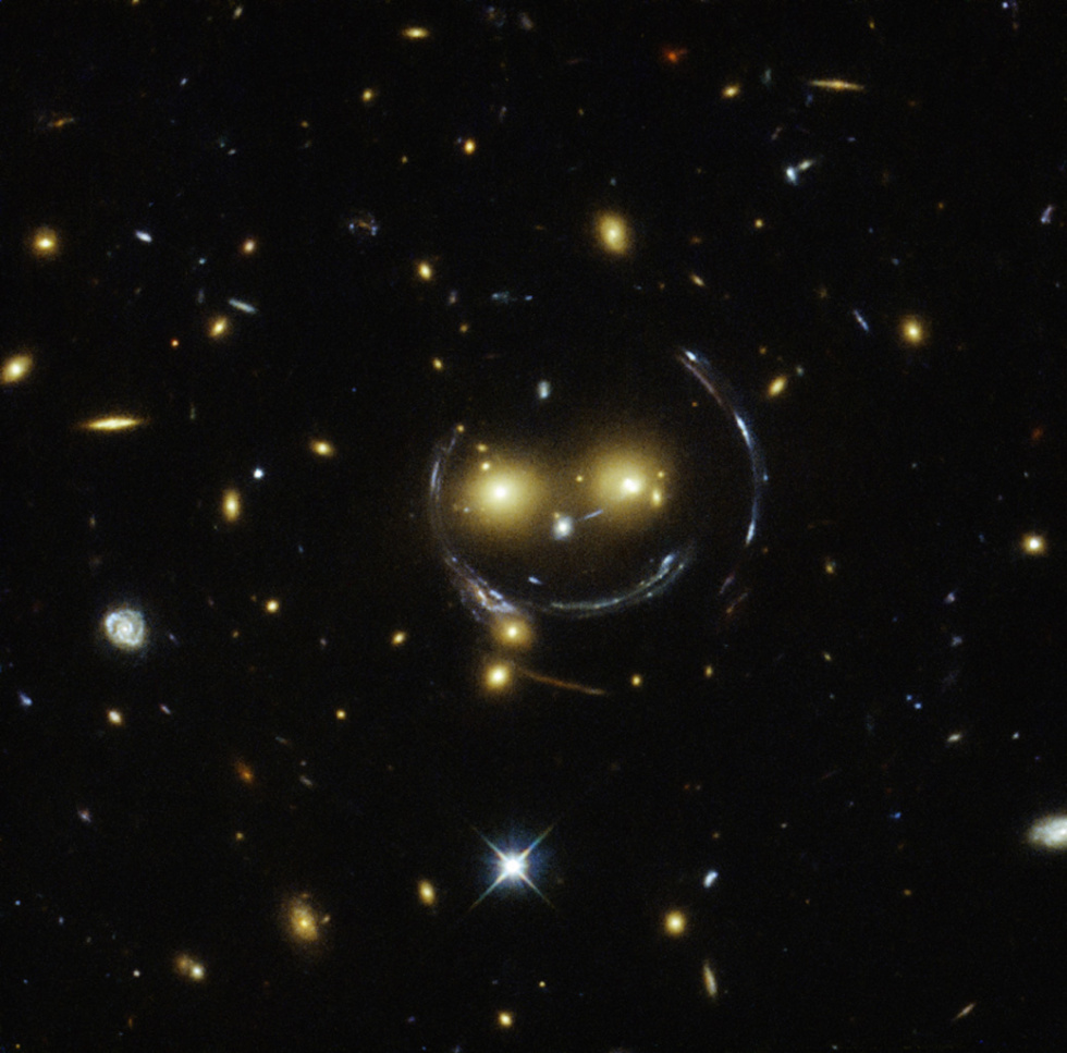 The galaxy cluster SDSS J1038+4849, with bright galaxies creating the eyes and nose, and gravitational lensing effects causing the curved features.