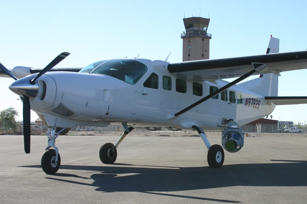A Cessna passenger plane equipped with a Wescam stabilized surveillance sensor. The FBI has a fleet of aircraft equipped this way.