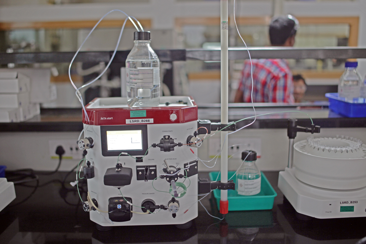 That tall, white object clamped to the right of the machine is a typical column. A source of the solution that flows through the system is the bottle at top.
