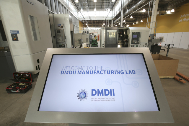 "Opening day at the DMDII Manufacturing Lab, where designs from the Digital Manufacturing Commons can be ""printed"" during trials to physical prototypes. The lab's complex machine cell, with equipment provided by DMG MORI, includes multi-axis milling machines that can cut away material from multiple directions in a single setup."