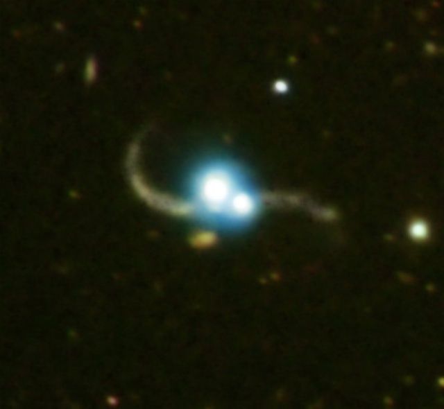 Composite X-ray and optical image of two galaxies with quasars merging (this pair is much closer to Earth than the ones included in the new study). Taken by the Chandra X-ray observatory. The X-ray part of the image, in blue, shows the two quasars, which outshine their host galaxies. The optical part, in yellow, shows gas and dust trailing off the two galaxies after being gravitationally stripped.