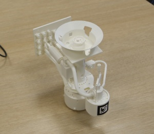 A 3D-printed model of a well component from the lab, with a QR-like tag for easier recognition by the manual application.