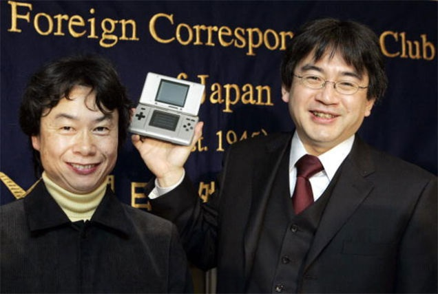 Iwata (right) and Shigeru Miyamoto show off the new Nintendo DS in 2004.