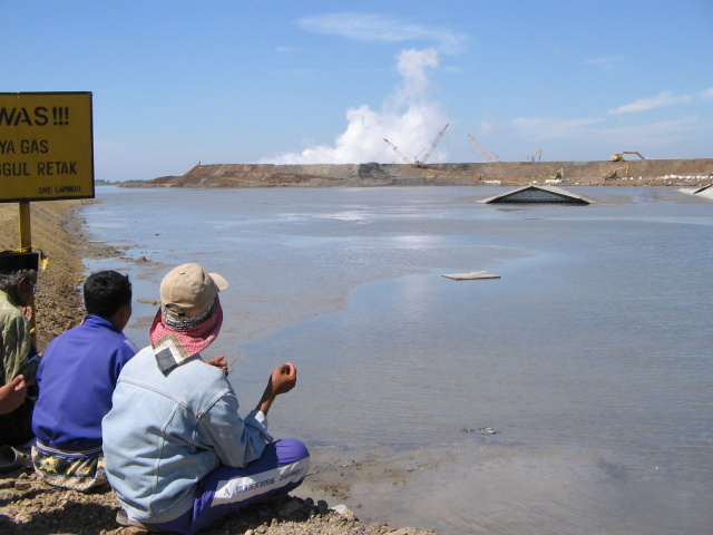 People praying for the eruption to stop in 2007. The buildings peeking through the mud had been factories.