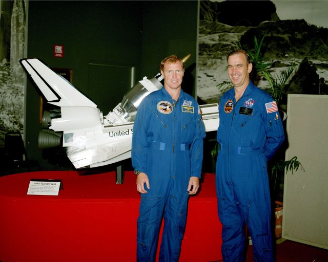 "Astronauts John Fabian and Dave Walker pose in front of what almost became their ""ride"" during a Shuttle-Centaur rollout ceremony in mid-1985."