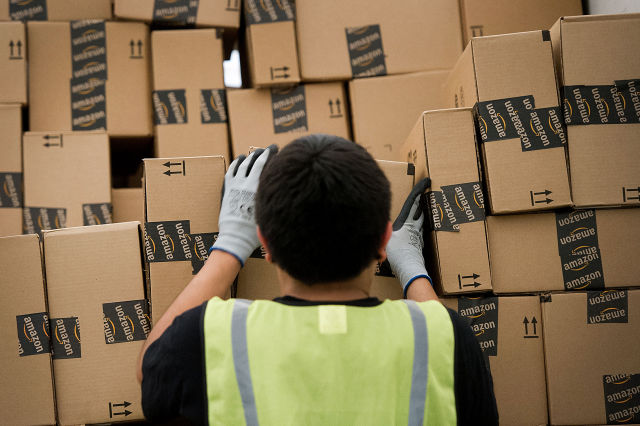 An employee loads a truck at an Amazon.com Inc. distribution center in Phoenix, Arizona in 2012. Photographer: David Paul Morris/Bloomberg via Getty Images