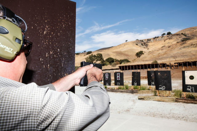 Jim Schaff of Yardarm demonstrates the sensor his company developed in place on a Glock 22 at a shooting range in San Jose, California, on Thursday, September 10, 2015. The sensor can alert dispatchers when an officer pulls his or her weapon and when shots have been fired and transmit the location back to dispatch.