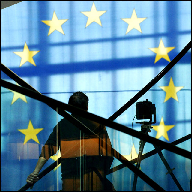 The silhouette of a photographer and his camera are shown against an EU flag.