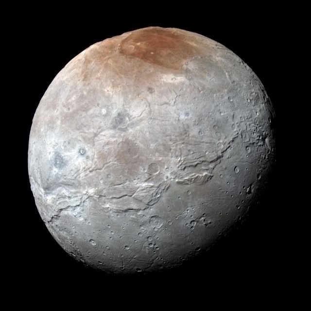 An enhanced color image shows that Charon doesn't have quite the same diverse coloration as Pluto. The one reddish region at top has been named the Mordor Macula.