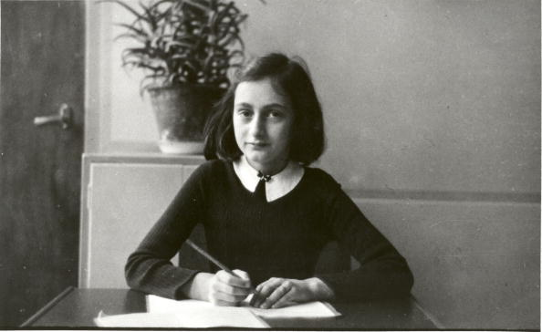 Anne Frank (1929 - 1945) writes at her desk in Amsterdam prior to her and her family going into hiding during World War II.