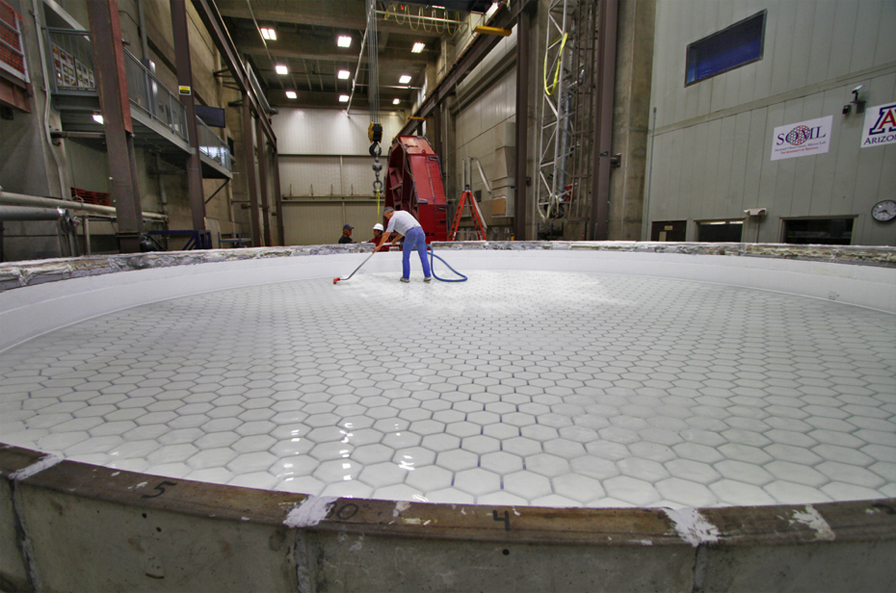 A worker attends to one of seven large mirrors that will comprise the Giant Magellan Telescope.