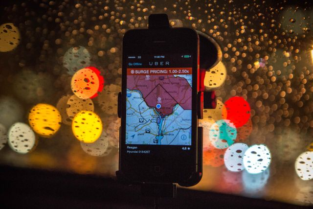 The Uber driver app on the windshield of UberX driver.