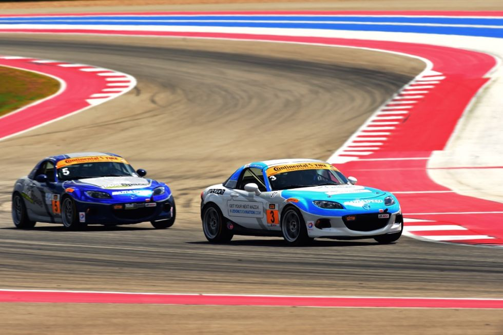 The #3 CJ Wilson Racing Mazda MX-5 leads its sister car through one of the Circuit of the Americas' brightly painted turns.
