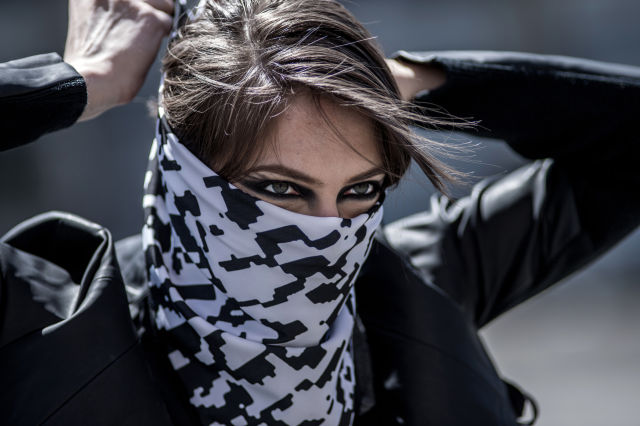 A black-and-white bandanna printed with a blocky, digital pattern reminiscent of the common Arabic keffiyeh is one item in the Backslash kit, a package of devices that help protesters stay safe and connected during demonstrations. The bandanna's pattern can store messages that can be revealed with the Backslash app.