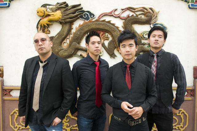 """Portrait of Asian-American band The Slants (L-R: Tyler Chen, Ken Shima,  Simon """"Young"""" Tam, Joe X Jiang) in Old Town Chinatown, Portland, Oregon, USA on 21st August 2015. (Photo by: Anthony Pidgeon/Redferns)"""