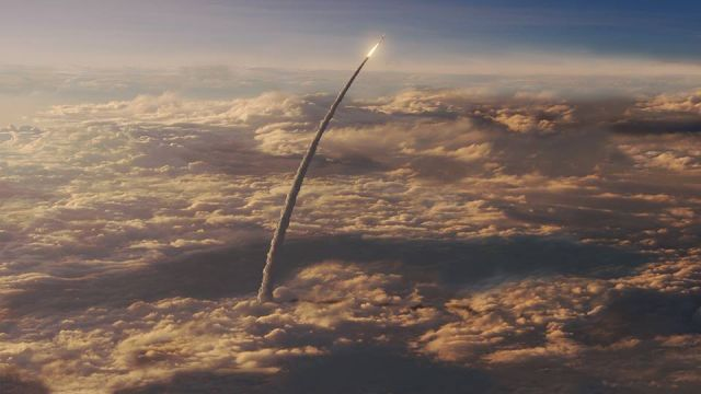 An artist's concept of the Space Launch System rocket ascending through the clouds.