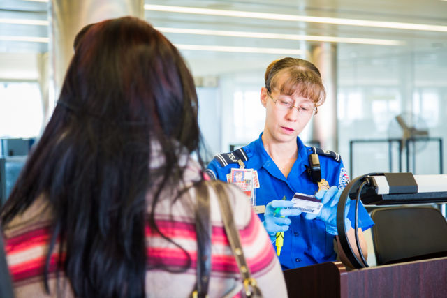 A Transportation Security Officer reviews the identification of a passenger at one of the checkpoints at Baltimore/Washington International Thurgood Marshall Airport (BWI).