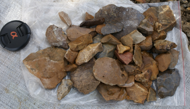 A few of the hundreds of stone tools that researchers found at the Talepu excavation in Sulawesi, Indonesia. Camera lens cap is included for size comparison.