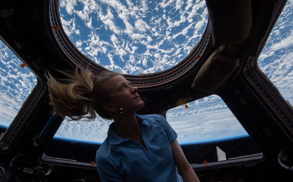 Astronaut Karen Nyberg  gazes out of the International Space Station's cupola. A company, NanoRacks, wants to add a commercial airlock to the same module.