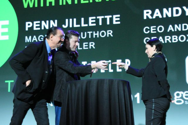 Jillette (left) and Pitchford (center) perform a card trick on stage with an audience volunteer.