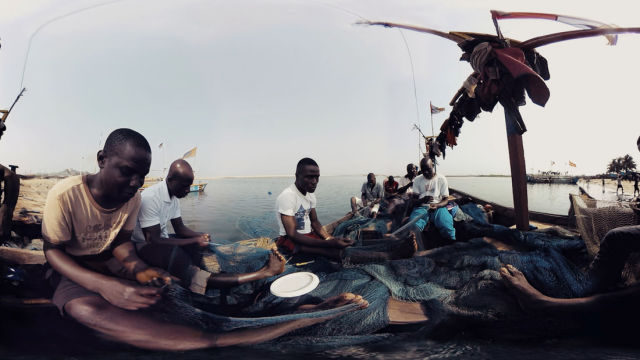 A captured-from-VR shot of the short film <em>Waves of Grace</em>. This exploration of Liberia does little to direct its action, instead dropping a 360-degree camera into various scenes and forcing viewers to manually hunt for visual content around busy scenes.