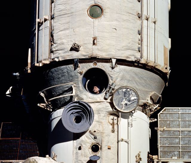 Valery Polyakov looks out of Mir as space shuttle Discovery approaches the space station in 1995.