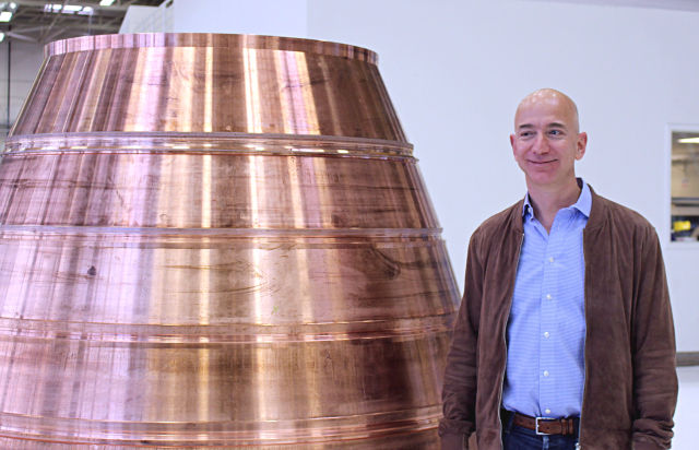 Jeff Bezos stands next to a nozzle of a BE-4 engine in his Blue Origin rocket factory.