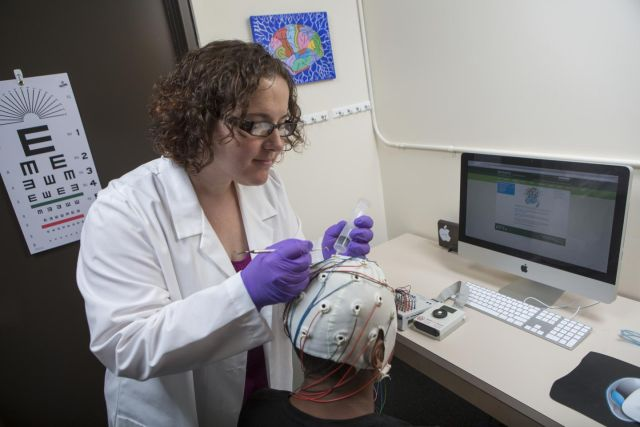 Sarah Laszlo puts an EEG headset on a research participant's head.