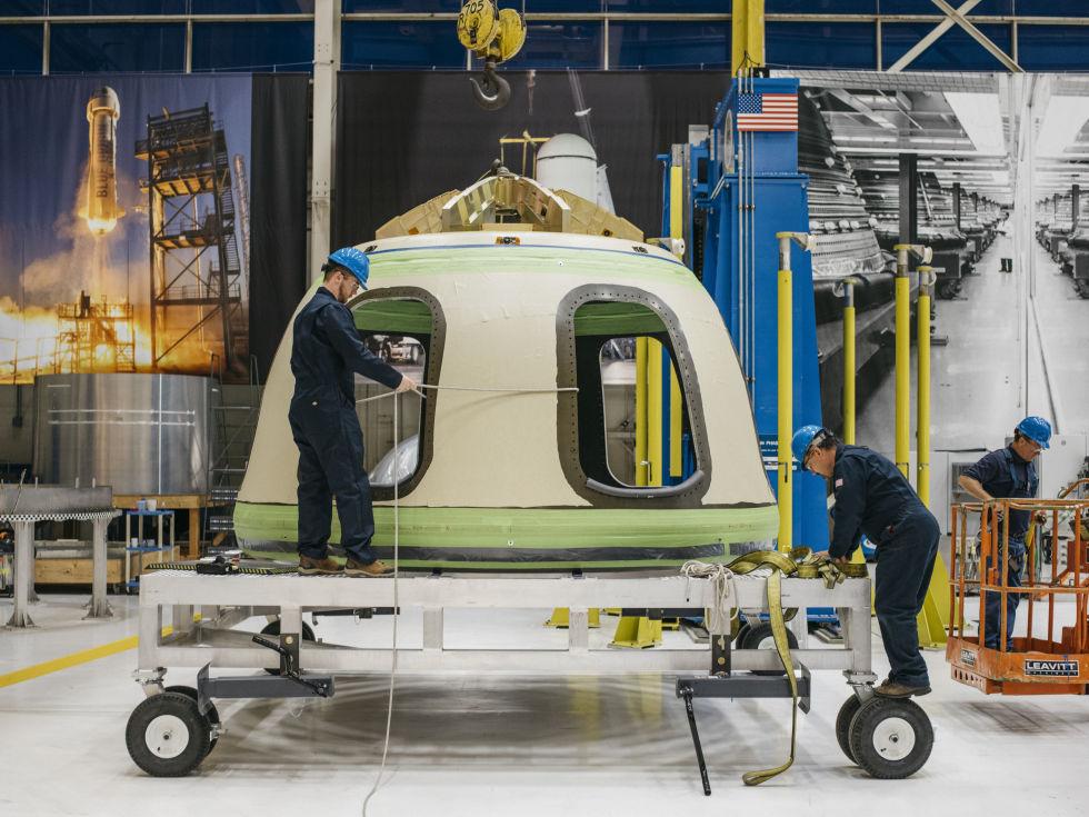 Engineers work on a New Shepard capsule in March inside Blue Origin's rocket factory near Seattle.