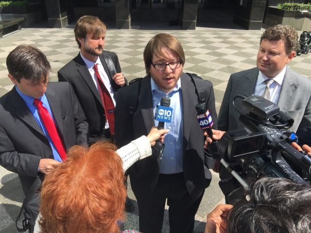 Matthew Keys talks to reporters after he was sentenced in April 2016 to two years in prison, surrounded by his lawyers, including Mark Jaffe (far left).