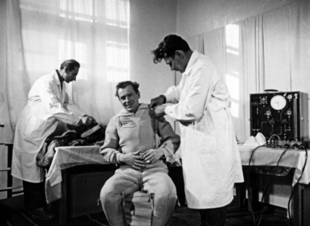 Titov being helped with his space suit in preparation for his flight in the Vostok 2 mission. This is another still from the documentary film <em>To the Stars Again</em>.