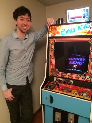 Wes Copeland poses with the <i>Donkey Kong</i> machine he used to set his record.