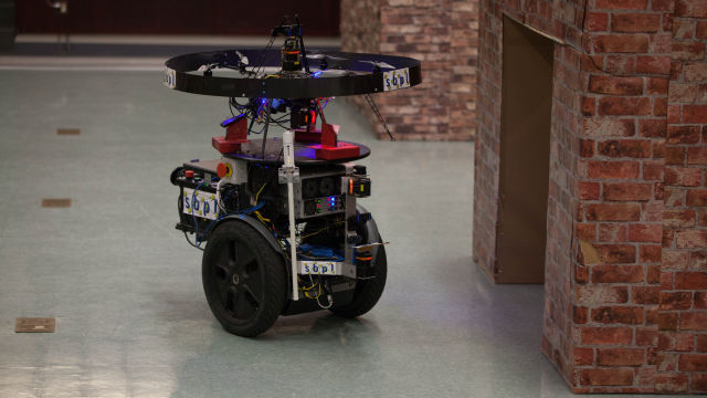 The Unmanned Tactical Autonomous Control and Collaboration (UTACC), a ground robot and small drone team, patrols a simulated town indoors in Ellis Hall at Marine Corps Base Quantico.