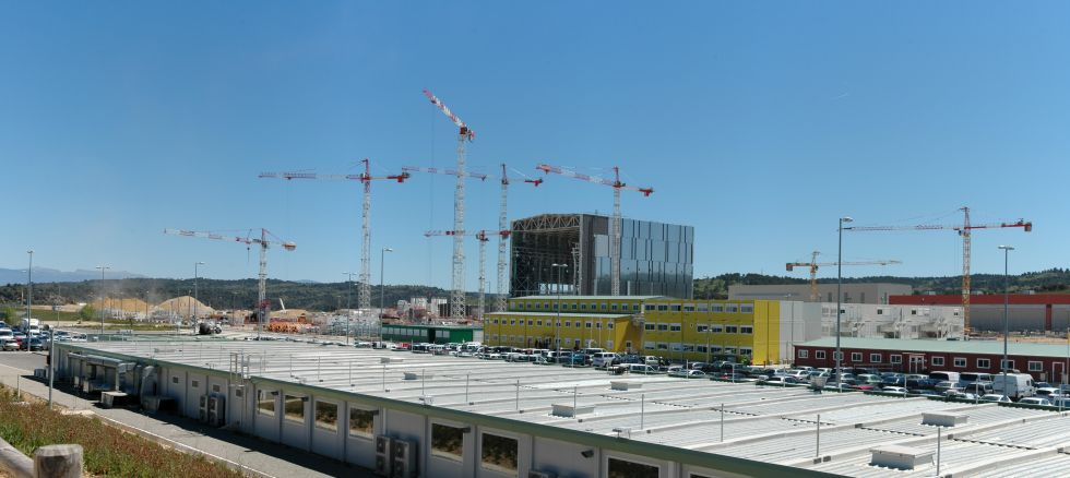 Behold ITER—EUROfusion's evidently preferred child. Foreground buildings: Contractors Canteen, Changing Rooms, Showers, etc. || Green, Yellow, and Red buildings: Contractors' Offices || White Building: Canteen and Infirmary for Contractors || Tall building: Assembly Hall || To the right of the Assembly Hall and behind the other buildings: Cryostat Assembly Site.