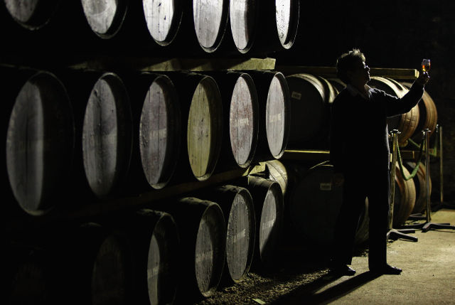 Maureen Stronach, an employee at Diageo's Dalwhinnie distillery, views whiskey drawn from a cask in the store room on April 21, 2011.
