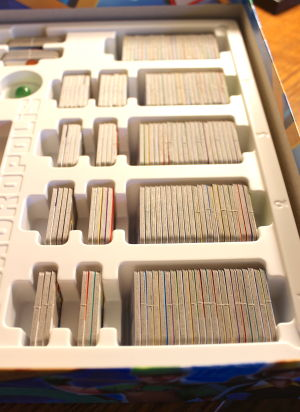 The box insert holding the tiles, grouped by round and by play mode.
