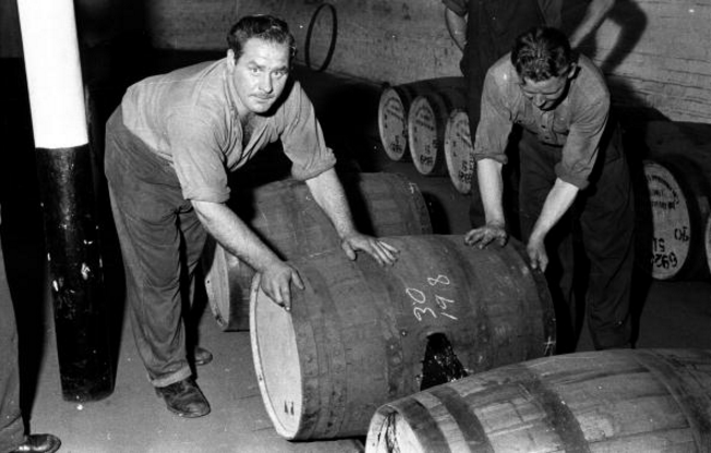 "Workers rolling barrels of whiskey along the floor at Johnnie Walker's distillery in the Scottish industrial town of Kilmarnock. The Johnnie Walker company's slogan is ""born 1820—still going strong."""
