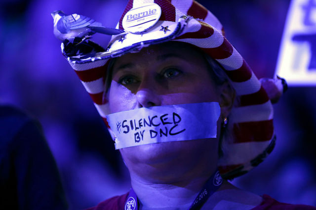 An attendee at the first day of the Democratic National Convention protests the DNC's treatment of Bernie Sanders, as hinted at by e-mails exposed by an alleged Russian hack.