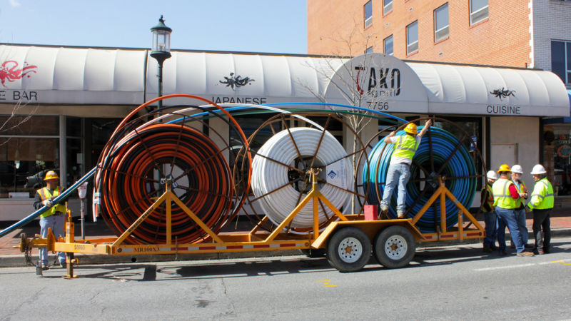 Workers with massive spools of fiber optic cable.