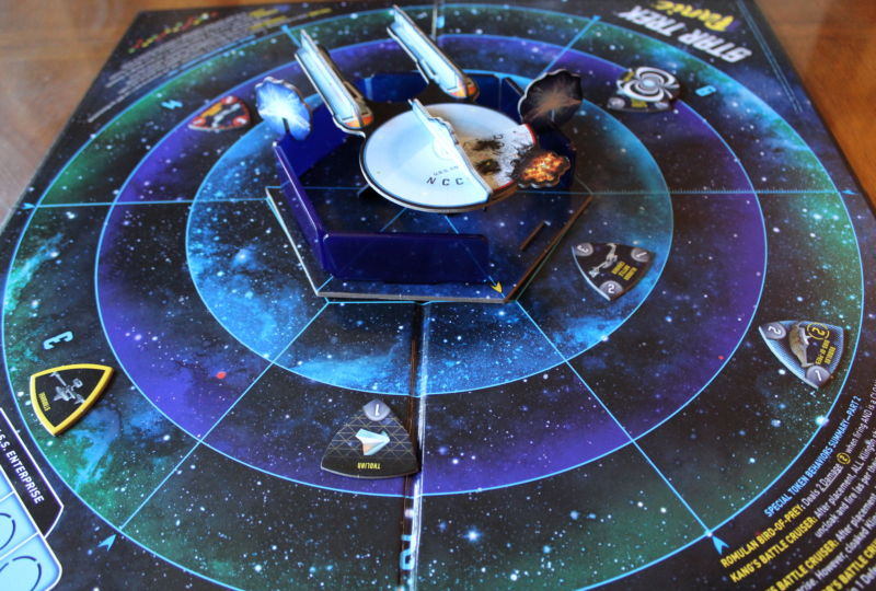 The basic game setup: ship in the center and enemies approaching from six sectors, ring by ring. One shield is already down; two others have taken damage. One hull section has been destroyed.