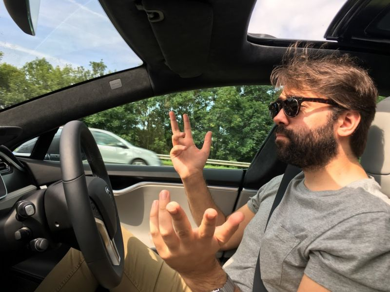 A hirsute Sebastian using autopilot in a Tesla Model S.