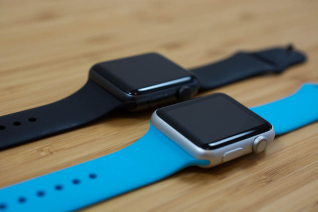 Series 2 (black band) next to Apple Watch Series 1 (blue band).