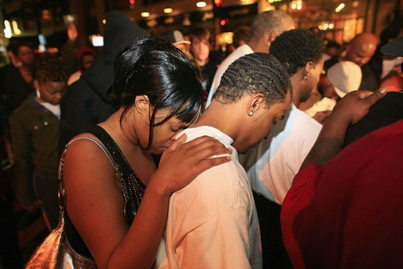 MILWAUKEE, WI: A woman rests her head on the shoulders of a man as a group of supporters stop and pray after a verdict of not guilty came back on four of the five charges for the three former police officers who stood trial for the beating of Frank Jude Jr.