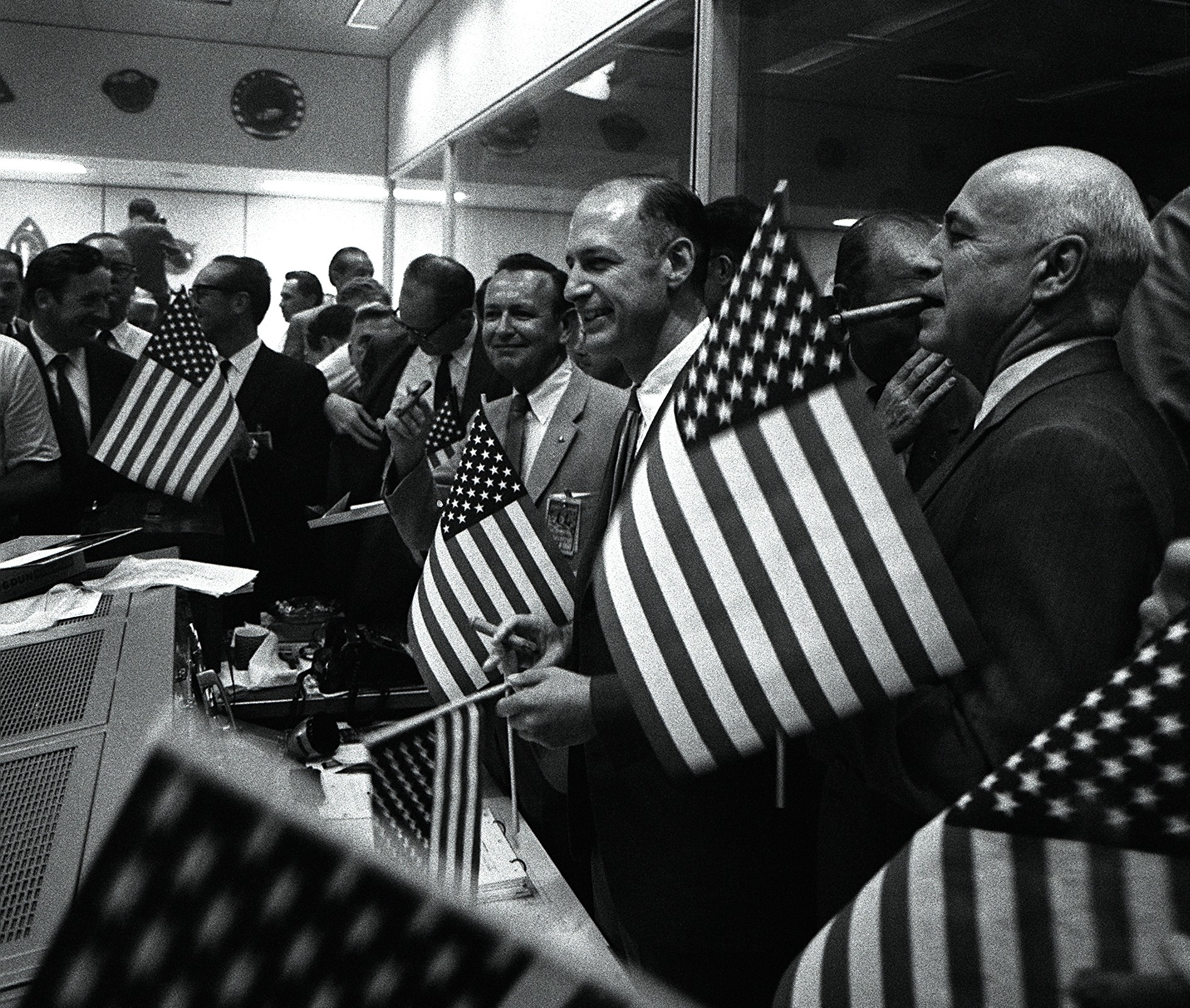 Key officials celebrate the successful conclusion of the Apollo 11 lunar landing mission. Robert R Gilruth is at the far right, George Low, Manager, Apollo Spacecraft Program, is next to him and Chris Kraft Director of Flight Operations is in the center.