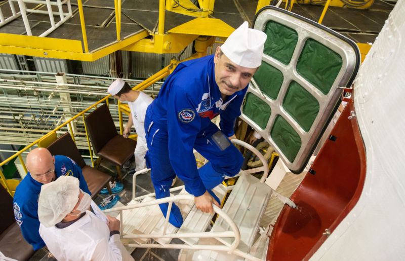Cosmonaut Mikhail Kornienko climbs the stairs to enter the Soyuz TMA-16M spacecraft during the final check of the spacecraft, with NASA Astronaut Scott Kelly.